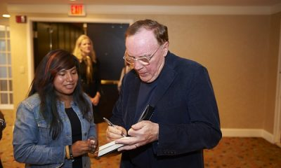 James Patterson signing a book for a VIP guest